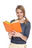 Cheerful girl reads book Stock Photos