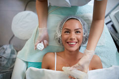 Cheerful girl is receiving facial treatment by beautician. Lady lying and smiling 4D laser lifting face royalty free stock photos