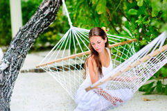 Cheerful girl relaxing in hammock. Portrait of cheerful girl relaxing in hammock in tropical garden Royalty Free Stock Images