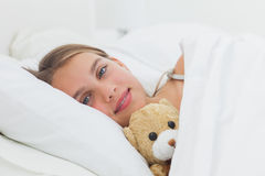 Cheerful girl relaxing with her teddy bear Royalty Free Stock Image