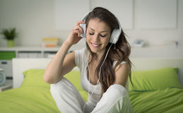 Cheerful girl relaxing at home. Cheerful girl with headphones relaxing at home, she is sitting on the bed and listening to her favourite music Stock Photography