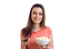 A cheerful girl with remote control from the tv and popcorn smiles. Isolated on white background Royalty Free Stock Photography