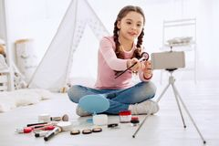 Cheerful girl reviewing eye shadows for her beauty blog. Connoisseur of cosmetics. Pleasant cheerful girl reviewing eye shadows for her beauty blog and filming Royalty Free Stock Images