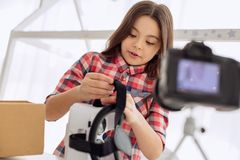 Cheerful girl reviewing VR headset in her vlog. Modern technologies. Pleasant pre-teen girl reviewing a virtual reality headset while recording a video blog for Stock Photos
