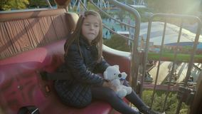 Cheerful girl rides on a roundabout, smiles and looks around with her teddy at sunset in slo-mo stock video footage