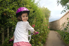 Cheerful girl riding a bike stock image