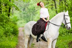 Cheerful girl riding horse Stock Photos