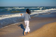 Cheerful girl running on the beach, the concept of happiness stock photography