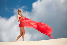 The cheerful girl on sand. The cheerful girl in red kapron costs on sand Stock Photography