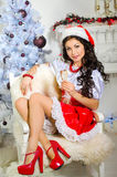 Cheerful girl in the Santa Claus hat. girl sitting on a chair wi. Th a glass of champagne Royalty Free Stock Photos