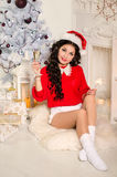 Cheerful girl in the Santa Claus hat. Girl sitting on the floor by the fireplace with a sparkler and a glass of champagne Royalty Free Stock Photography