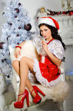 Cheerful girl in the Santa Claus hat.Woman drinking champagne at. Christmas Royalty Free Stock Photo