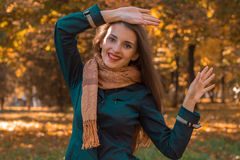 Cheerful girl in Scharfe stands in autumn Park and raised her hands up Stock Images