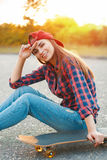 Cheerful girl in a shirt and a baseball cap sitting on the aspha. Lt with a skateboard.Beautiful sunset Stock Photo