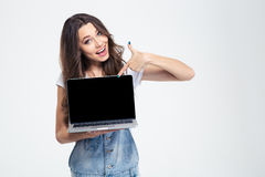 Cheerful girl showing blank laptop computer screen Royalty Free Stock Photography