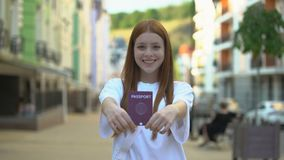 Cheerful girl showing international passport to camera, opportunities for travel. Stock footage stock video footage