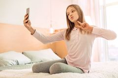 Cheerful girl showing V sign while taking selfie Royalty Free Stock Images