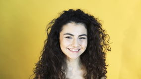 Cheerful girl shows emotion of reconciliation on yellow background 4K