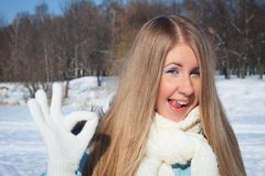 Cheerful girl shows tongue in park. Frosty morning in the park. Cheerful girl in a blue jacket and white scarf shows tongue in park. Frosty morning in the park Royalty Free Stock Image