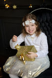 Cheerful girl sits in a chair with box of gold color in hands. Royalty Free Stock Image