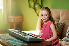 Cheerful girl sits near an  piano Stock Images