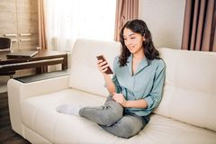 Young woman using smartphone at home. Cheerful girl sitting at home, using mobile phone, receiving text message from boyfriend, feeling joyfully and happily stock photography