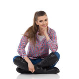 Cheerful Girl Sitting With Legs Crossed Stock Photo