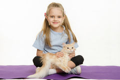 Cheerful girl sitting a rug and stroked the cat on her lap Royalty Free Stock Photo