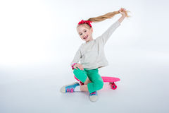 Cheerful girl sitting on skateboard on grey Stock Images