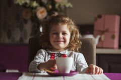 Cheerful girl sitting at the table Stock Images