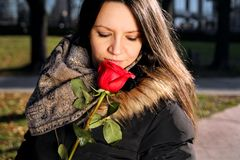 Cheerful girl smells red rose and enjoys the scent Stock Photos
