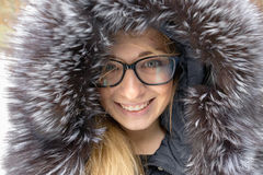 Cheerful girl with a smile in a fur hood. Royalty Free Stock Photos