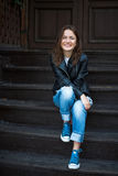 A cheerful girl in sneakers, jeans and a leather jacket sits on Stock Photography