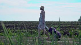 Cheerful girl with suitcase walking on road. From below shot of pretty young female pulling suitcase while walking on green field of grass stock video footage
