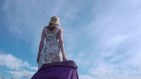 Cheerful girl with suitcase walking on road. A girl in a dress and with a suitcase goes with a suitcase. A wide-angle frame camera follows her stock video footage