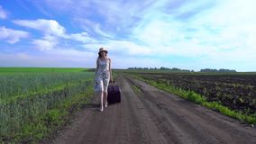 Cheerful girl with suitcase walking on road. A girl in a dress and with a suitcase walks along a rural road through a green field towards the camera stock video footage