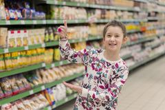 Cheerful girl in a supermarket shows on products. A girl of 8 years in a supermarket royalty free stock photos