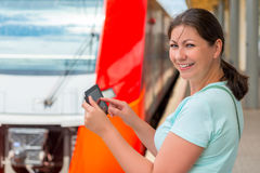 Cheerful girl with tablet computer is at the station Stock Images