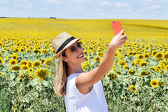 Cheerful girl taking selfie in a sunflower farm. Smiling young lady in the middle of a big sunflower farmland taking self portrait selfie with smartphone during Stock Photos