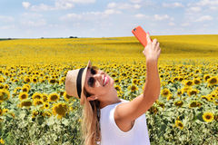 Cheerful girl taking selfie in a sunflower farm. Smiling young lady in the middle of a big sunflower farmland taking self portrait selfie with smartphone during Royalty Free Stock Photos