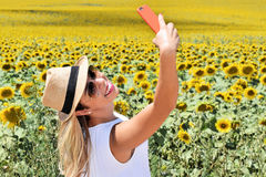 Cheerful girl taking selfie in a sunflower farm. Smiling young lady in the middle of a big sunflower farmland taking self portrait selfie with smartphone during Royalty Free Stock Photography