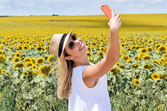 Cheerful girl taking selfie in a sunflower farm. Smiling young lady in the middle of a big sunflower farmland taking self portrait selfie with smartphone during Stock Image