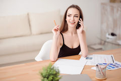 Cheerful girl talking on cell phone. Nice interlocutor. Cheerful content positive beautiful girl sitting at the table and talking on mobile phone while being Royalty Free Stock Photos