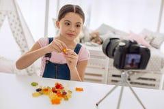 Cheerful girl tasting gummy bears in video blog Stock Photos