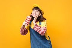 Cheerful girl teenager in french beret, denim sundress hold plastic cup of cola or soda put hand on cheek isolated on. Yellow background. People sincere stock photo