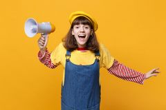 Cheerful girl teenager in french beret, denim sundress holding megaphone, spreading hands on yellow wall royalty free stock photo