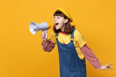 Cheerful girl teenager in french beret, denim sundress looking aside, scream in megaphone on yellow wall stock images