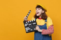 Cheerful girl teenager in french beret looking aside, holding classic black film making clapperboard isolated on yellow. Wall background. People sincere stock photo