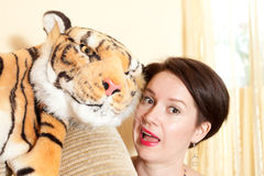 Cheerful girl with a toy tiger Royalty Free Stock Images