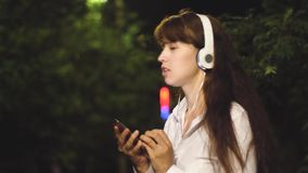 Cheerful girl travels in the night city. young girl in headphones and smartphone is listening to music, dancing and. Smiling at night in city park. close-up stock video